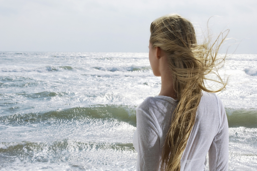 Rear view of a young blond woman looking at the ocean